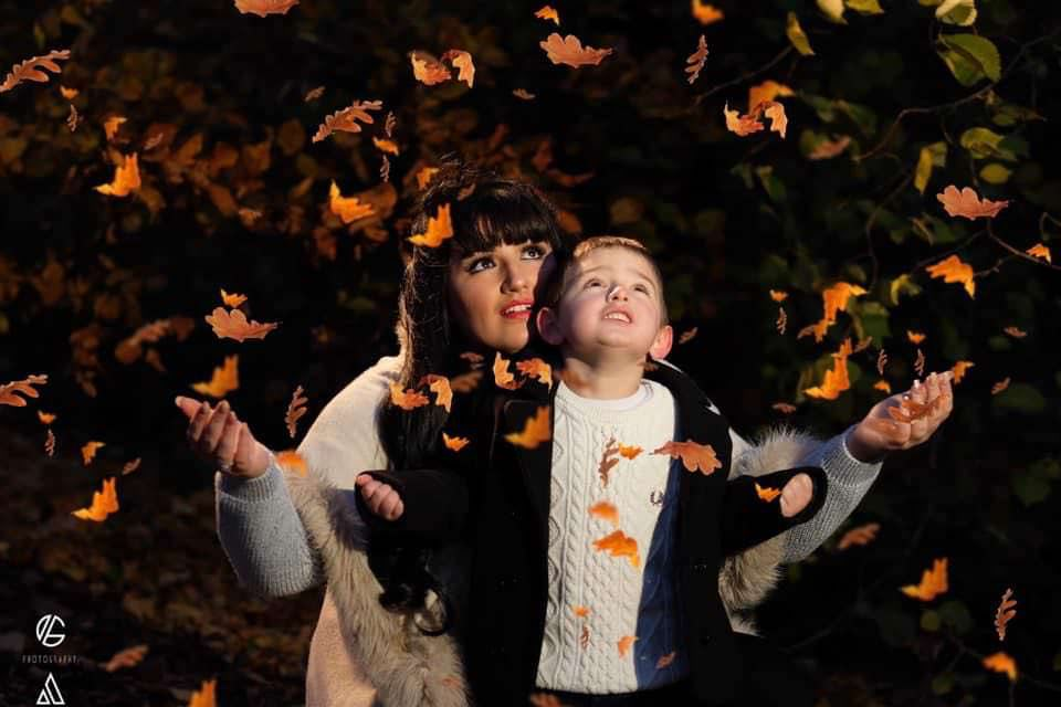 maddy and her son joshua playing with leaves
